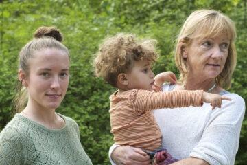 Ältere Frau folgt mit Blick dem Fingerzeig des Kleinkindes in ihrem Arm. Junge Frau steht daneben und blickt in die Kamera