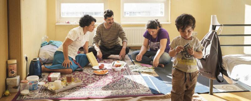 Eine Frau berät eine Familie mit einem Kind in einer Unterkunft