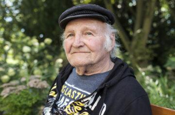 Ältere Mann sitz auf Parkbank und lächelt