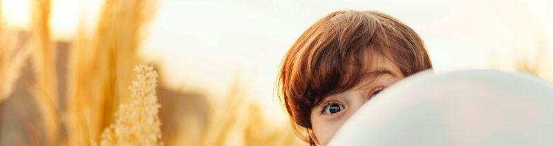 Junge schaut hinter bunten Luftballons hervor