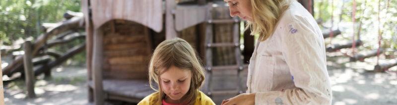 Ein Mädchen und eine Frau stehen vor einem Tisch mit Farben und Pinseln