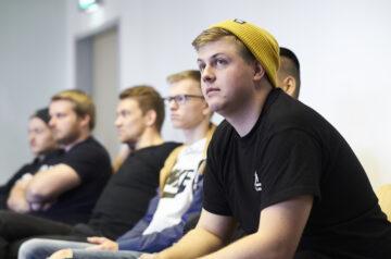 Mehrer Jugendliche junge Männer nehmen an einem Workshop Seminar teil und hören zu