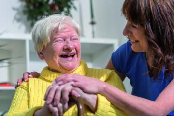 Lachende Oma mit ihrer erwachsenen Tochter