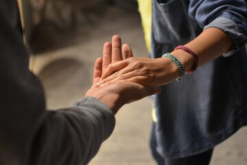 Frau fasst andere Person bei der Hand